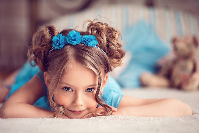 turquoise blue flower hair ornament, on the head of a smiling child, with two curly buns, on the sides of hr head, hairstyles for little girls