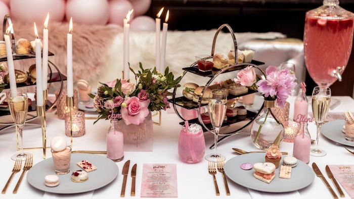 high tea table set up, with finger foods, macarons and various other desserts, 60th birthday party ideas for mom, pink and white theme, with flowers and candles