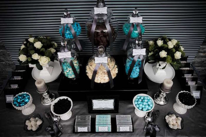 grey and teal snacks table, with a selection of vintage sweets in jars, and two bouquets of white roses, 60th birthday color