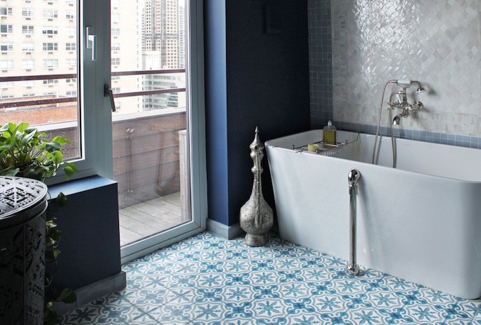 smooth modern bathtub in white, inside a room with a terrace, and blue and white tiles on the floor
