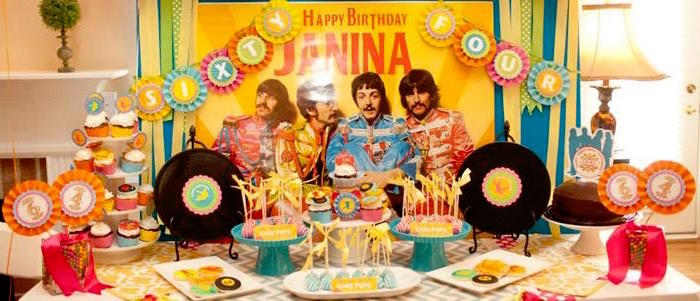 bright and colorful birthday set up, decorated with a customized beatles poster, and paper garlands, 60th birthday color, cupcakes and various other snacks
