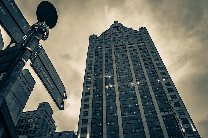 clouded dark grey sky, above a skyscraper, featuring details inspired by classical architecture, seen from a low angle