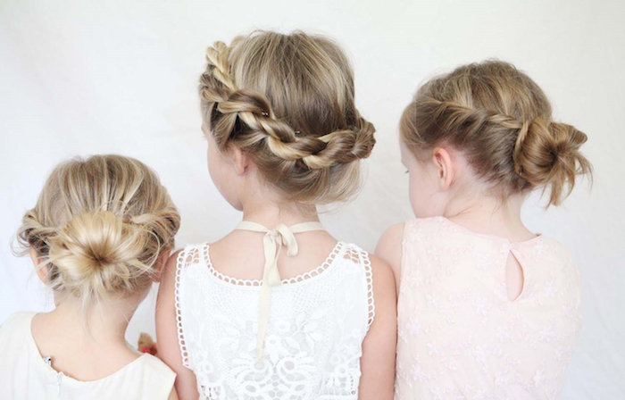 embroidered pale cream, and white formal dresses, worn by three small girls, with blonde hair, each styled in a different up-do, braids and buns, little girl hairstyles