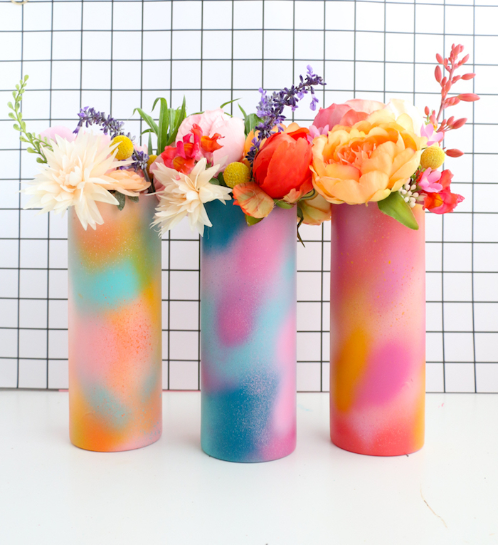 multicolored spray painted vases, placed on white surface, flower bouquets inside, thoughtful christmas gifts