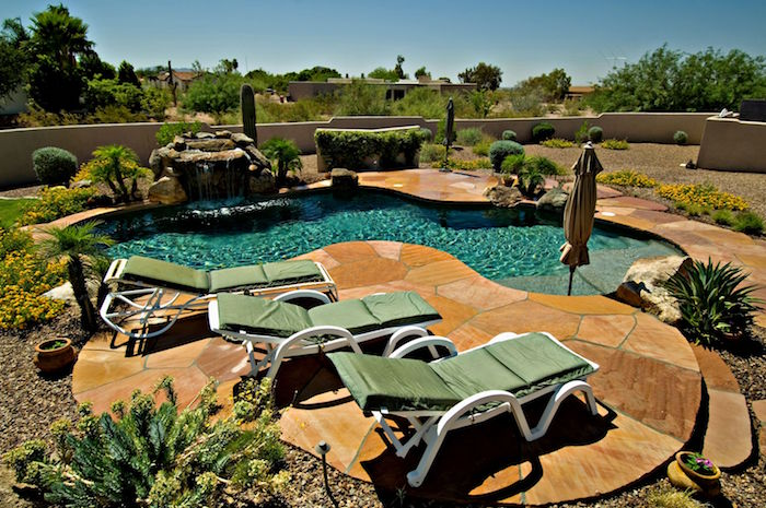 desert plants in a small garden, with pebbles and beige stone tiles, containing a small pool, and three green sun beds
