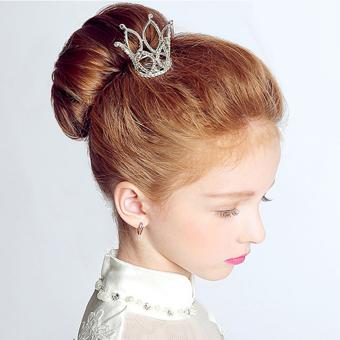 ornament shaped like a small, bejeweled silver crown, decorating the head of a young girl, with auburn hair styled in a bun, white formal dress