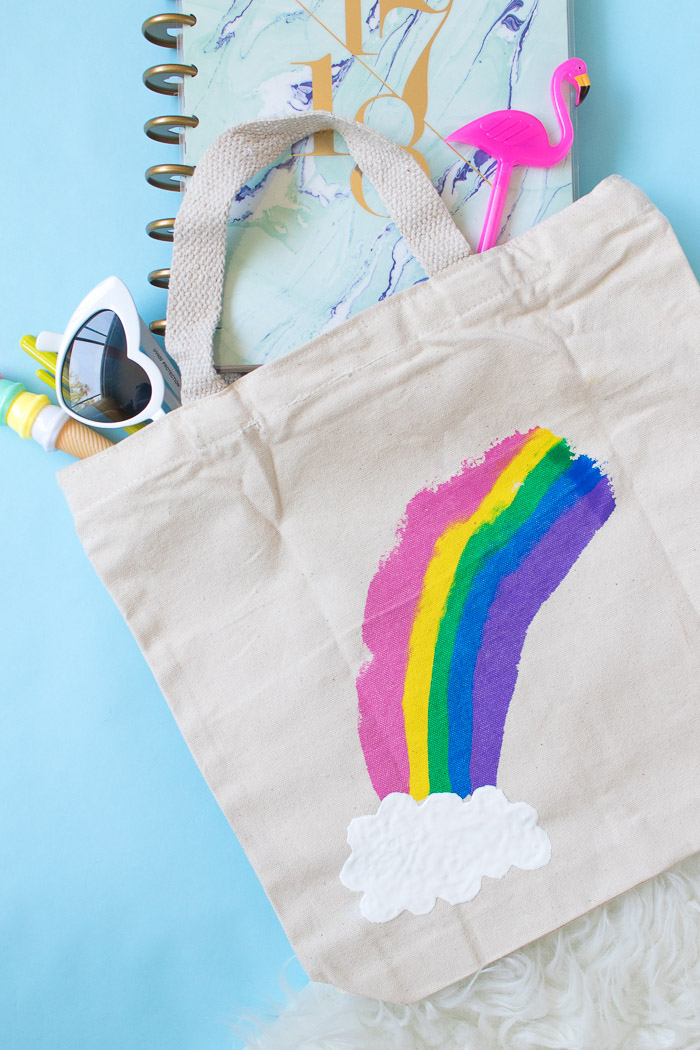 creative homemade gifts, tote bag with rainbow and cloud painted on it, placed on blue surface with notebook