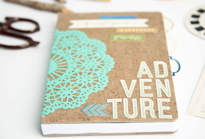 travel journal with the word adventure written at the front, creative homemade gifts, placed on white table