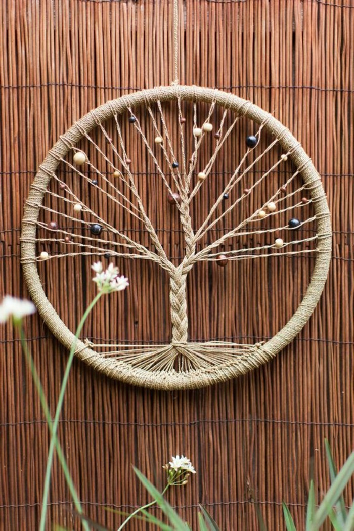 round decoration with a tree of life motif, woven with string, and decorated with beads, large dream catcher like ornament, on a rattan background