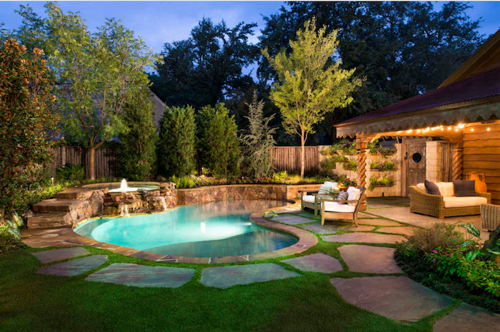 kidney shaped pool, with a small fountain, near a house with a lit porch light, small inground swimming pools, lawn with trees and shrubs