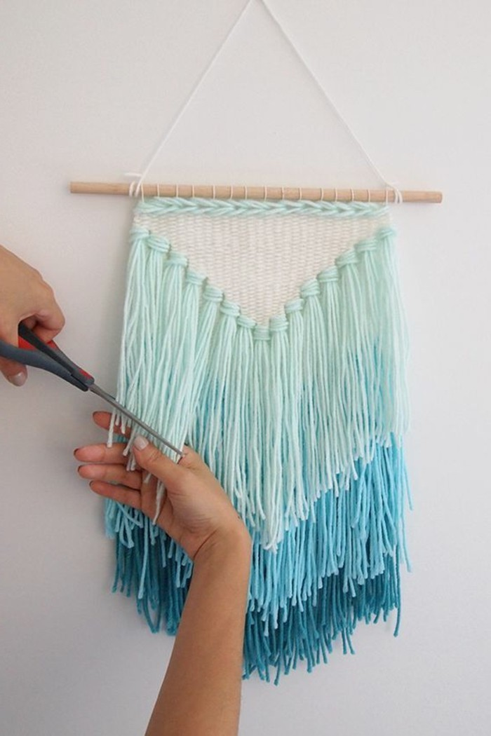 scissors held by a hand, trimming the tassels of a wall decoration, inspired by a dream catcher, in three shades of turquoise