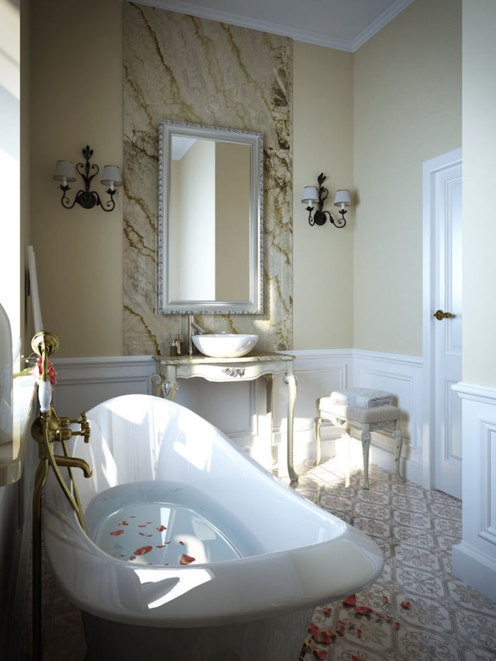 rose petals floating, in a half-filled white bathtub, antique style sink, and matching stool, ornate tiles in beige and white on the floor, nice bathrooms