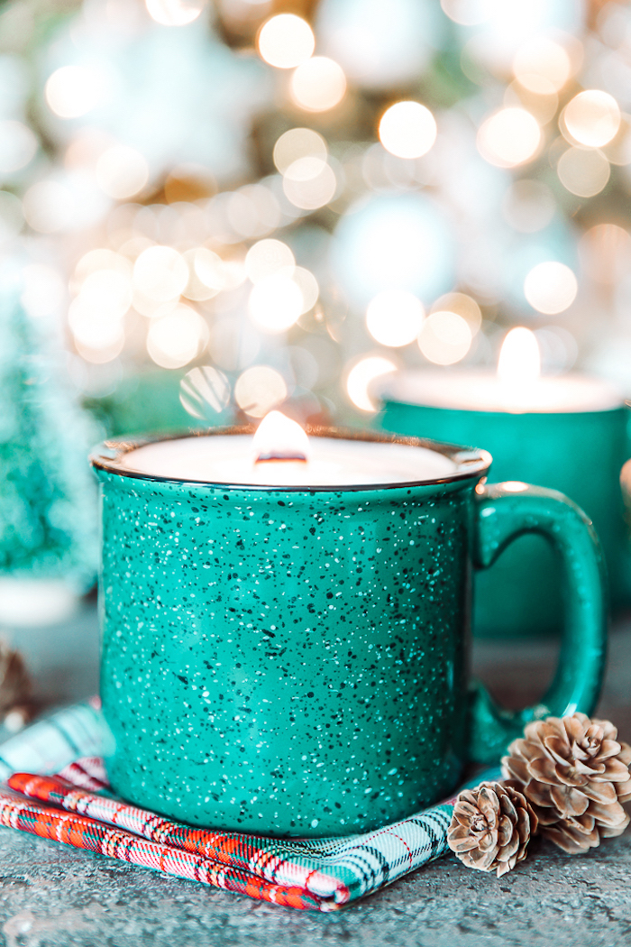 turquoise metal mug, candle inside, placed on a table cloth, homemade christmas gift ideas, pine cones on the side