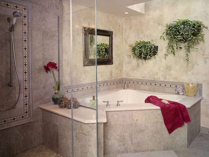 corner bathtub in white and grey, inside a room, containing a shower, two potted plants, a mirror and a red towel