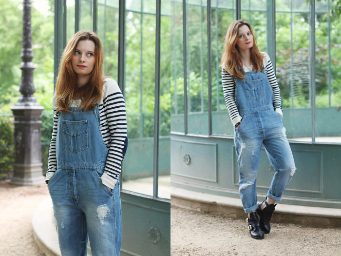 ginger-haired young woman, wearing vintage denim overalls, and a striped white and black jumper, standing with hands in her pockets