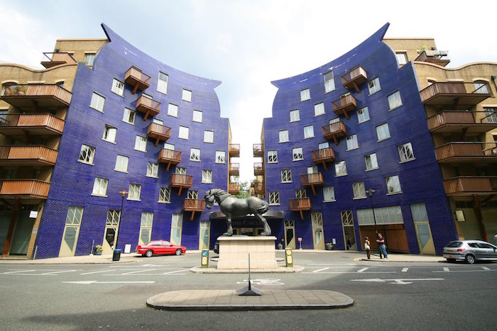 postmodernism characteristics, purple and beige symmetrical buildings, with square windows, and terraces with brown railings