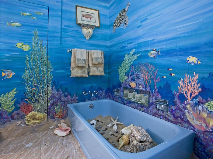 tropical fish and water turtles, seaweed and different kinds of corals, painted on the walls of a room, modern bathroom ideas, blue bathtub filled with sand, seashells and starfish