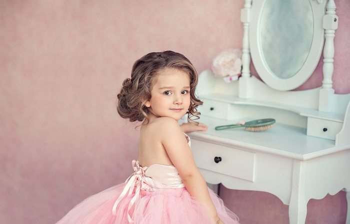 shoulder-length curled brunette hair, worn by a small girl, in a pale pink dress, with a tulle skirt, little girl haircuts, standing in front of a pale blue vanity