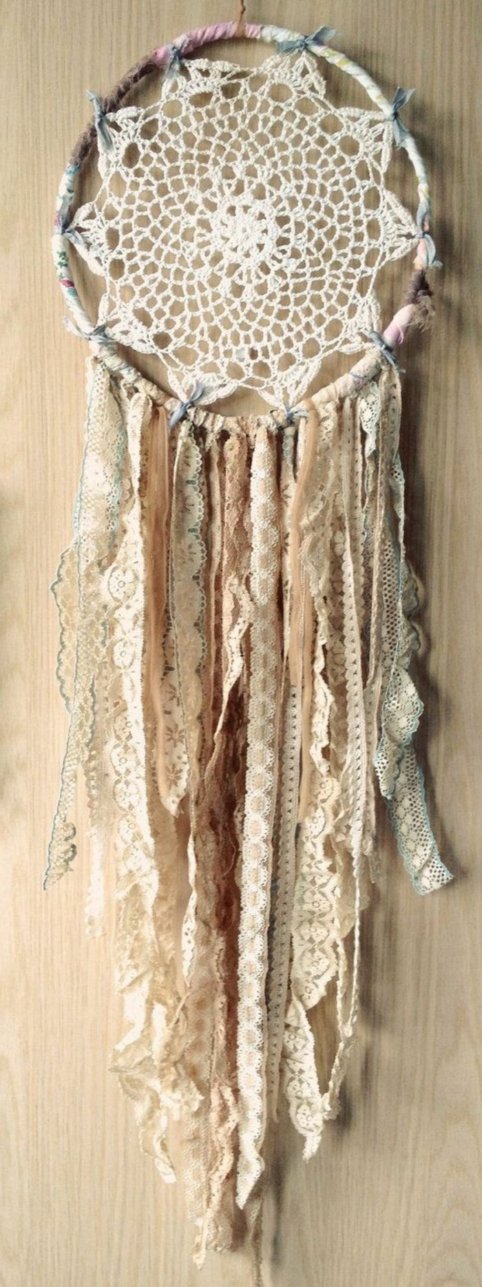 antique lace ribbons, in pale beige, cream and off white, attached to a boho dreamcatcher, with a crocheted doily, pictures of dream catchers, pale beige wooden background