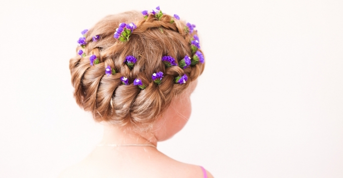blossoms in violet, decorating the braided head, of a dark blonde child, little girl hairstyles, seen from the back