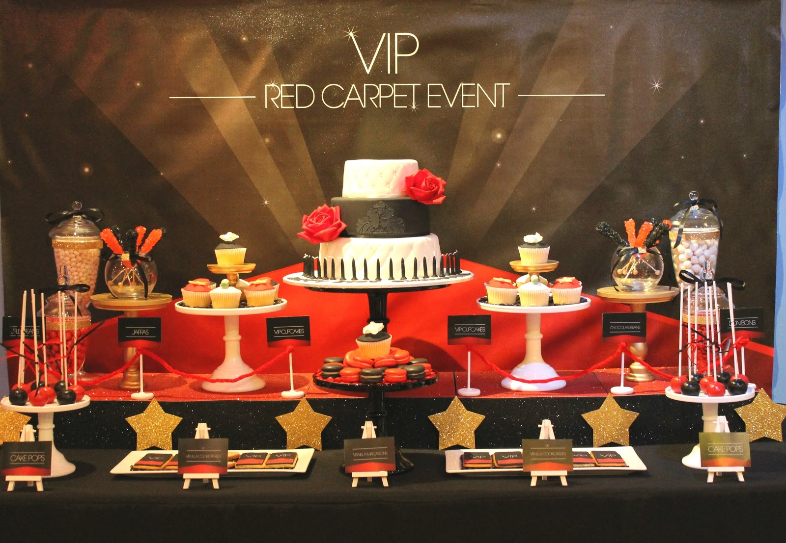 academy awards inspired 60th birthday decorations, with red carpet, and shimmering gold stars, three-layered cake in black and white, a selection of sweets