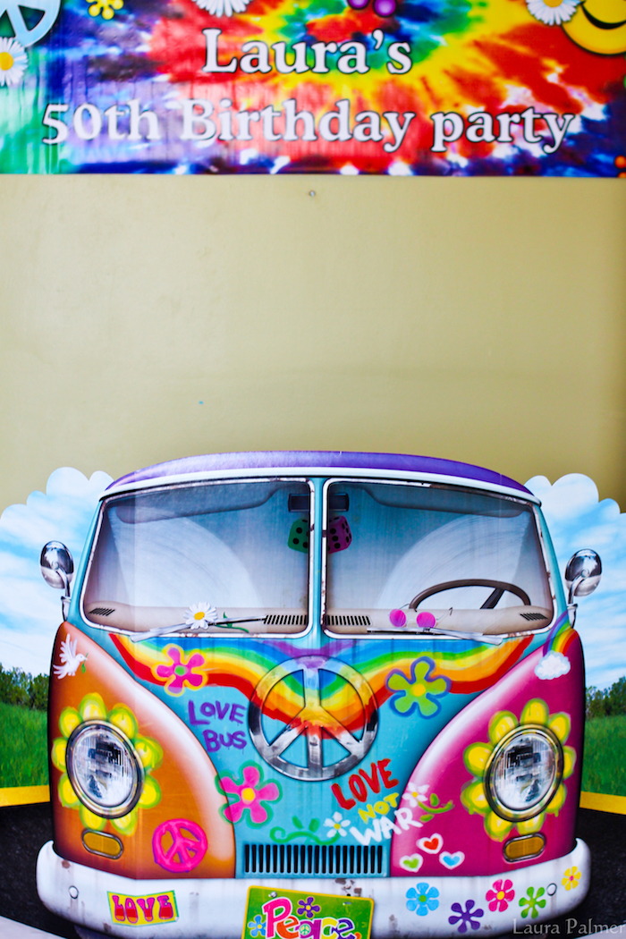 cardboard cutout of a hippie van, decorated with multicolored flowers, peace signs and graffiti, tie-dye effect birthday banner