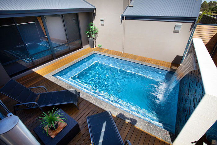 water pouring into a blue, rectangular swimming pool, from a waterfall-like faucet, small backyard pool ideas, patio with sun beds and a table, house with large windows