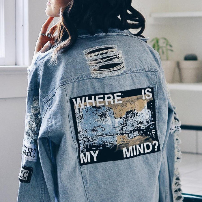 statement denim jacket, with rips and faded patches, worn by brunette woman, with her face turned away, where is my mind, written with white letters