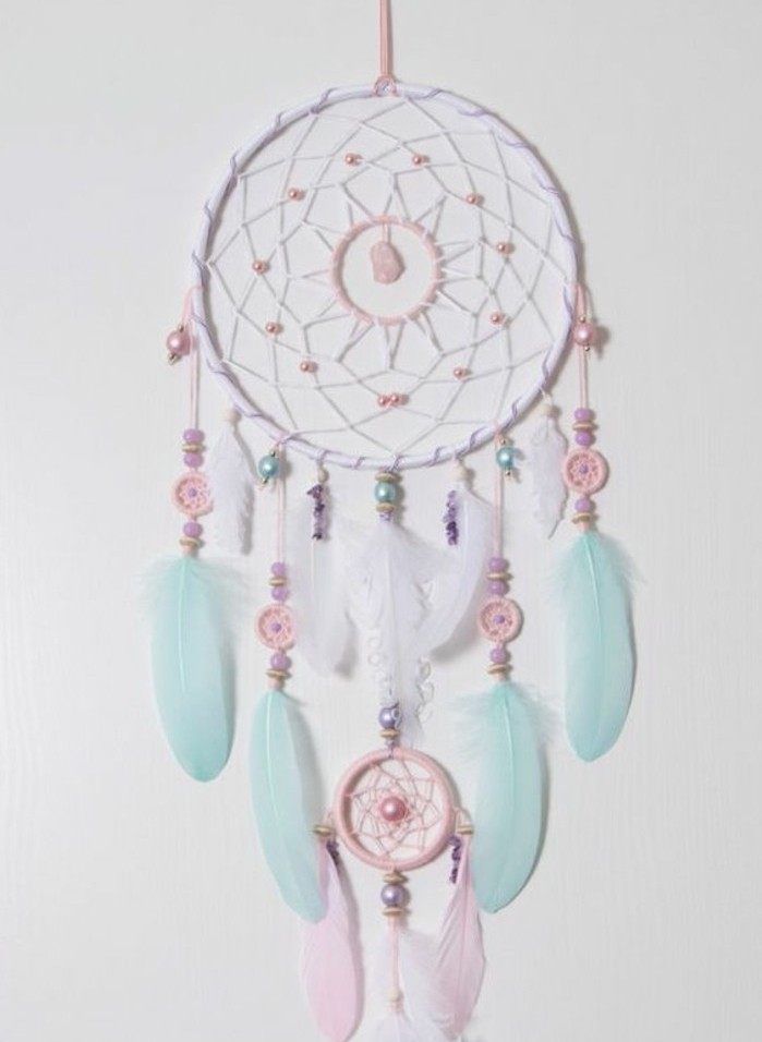 baby pink and white, and pastel turquoise feathers, small ornaments and beads, decorating a white dreamcatcher, how to make a dreamcatcher
