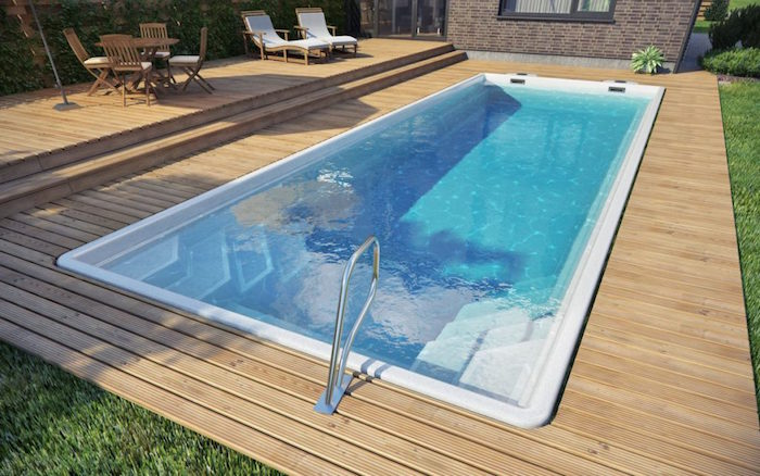 white rectangular pool, surrounded by pale wooden planks, pool patio ideas, garden table with four chairs, two sun beds