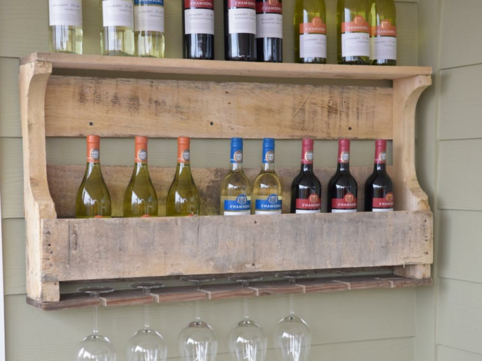 seventeen bottles of red, and white wine, on a diy wine rack, handmade gift ideas, five wine glasses
