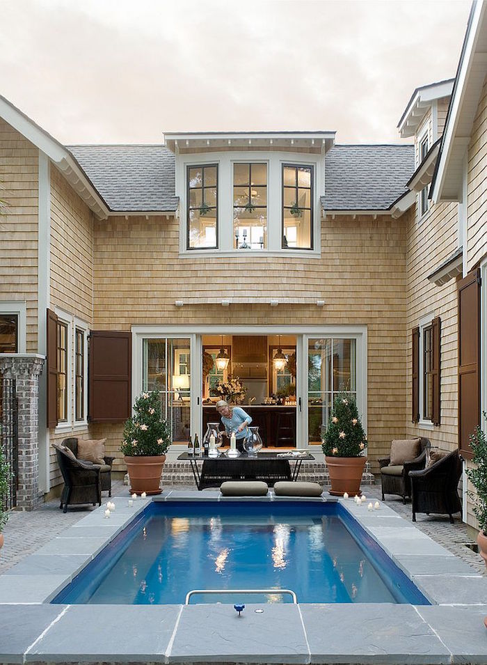 candles decorating the edges, of a small blue rectangular pool, near a house with open glass doors, woman lighting a dandle nearby