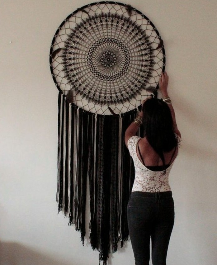 intricate woven pattern in brown, on a large dream catcher, with black tassels, dark-haired woman adjusting it, on a pale cream wall