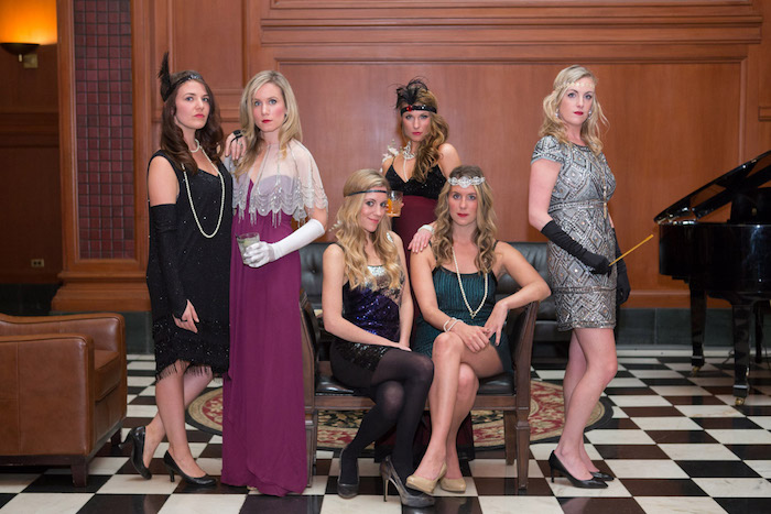six young women, wearing evening dresses in different colors, decorated with vintage accessories, gatsby dress, feathered headbands and long gloves, a sheer lace shrug, and long pearl necklaces