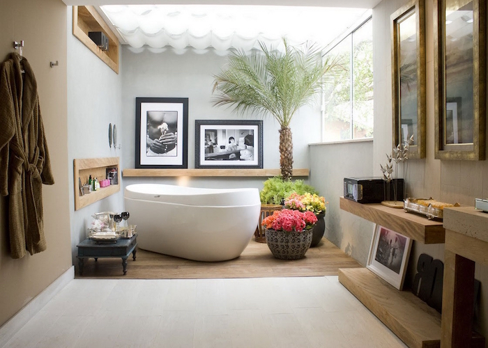 palm tree and several potted plants, in a bright room, floor partially covered in off-white tiles, and wooden laminate, pale grey and beige walls, decorated with framed images, modern bathroom ideas, led effect glowing ceiling