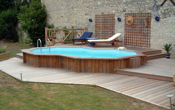 teal colored pool, lined with wooden planks, in a garden with a stone wall, decorated with wooden details