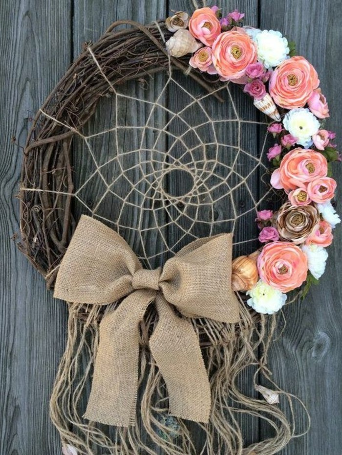 burlap bow and tassels made of plain string, decorating a wreath, adorned with pink and white flowers, several conch shells, and a dreamcatcher net, big dream catchers, grey wooden surface