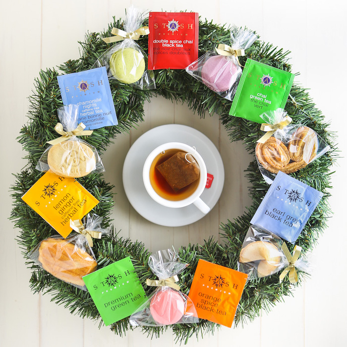 wreath made with tea bags and cookies, teacup in the middle, placed on white wooden surface, creative homemade gifts