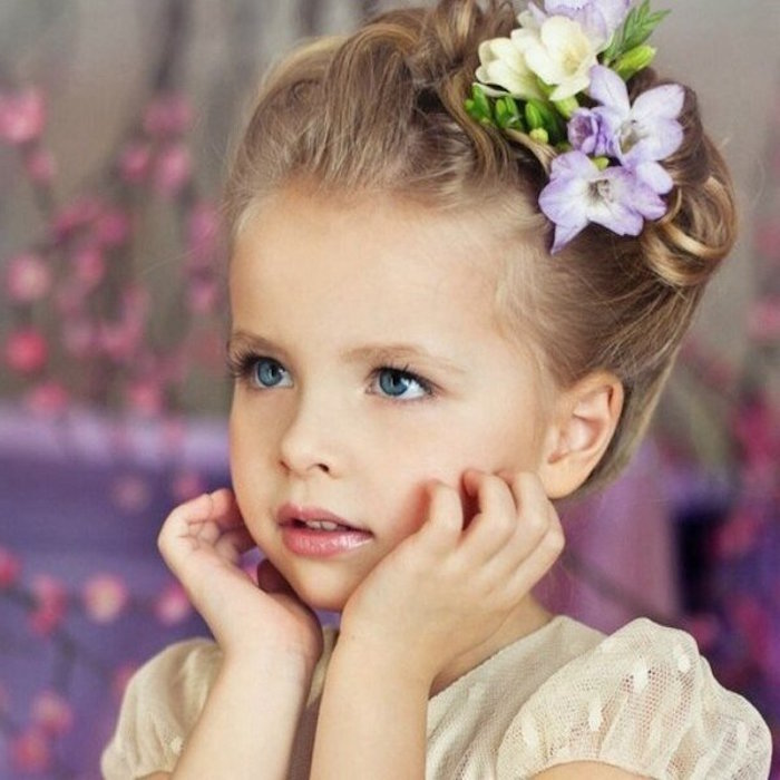 crocus-like flowers, in pale yellow and violet, decorating the dark blonde up-do, of a young, blue-eyed child, in a cream formal dress