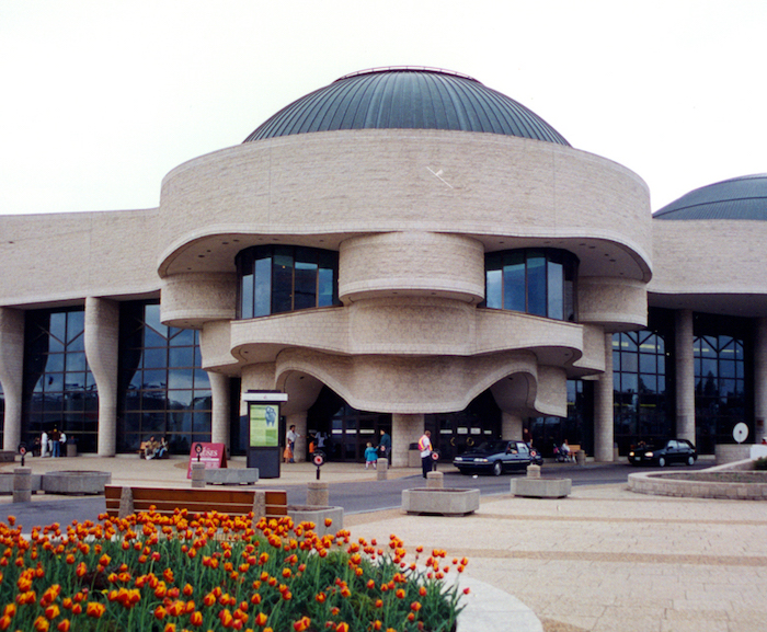museum of civilization in canada, pale beige building, with round and wave-like elements, lots of glass panels, and grey domes, modernism and postmodernism, tulip garden nearby