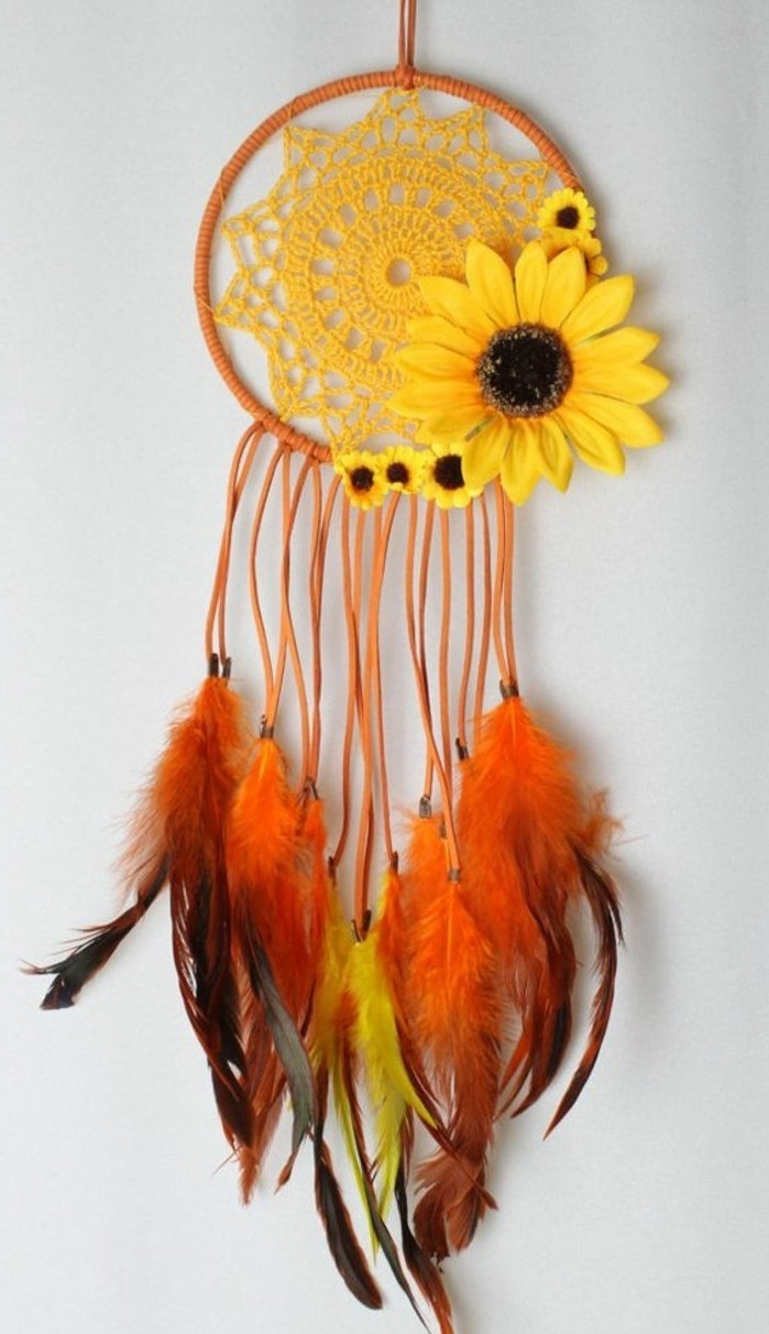 sunflower ornaments in different sizes, on an orange dreamcatcher, with a yellow crochet doily, and orange and yellow feathers, dreamcatcher designs, hanging on a white wall