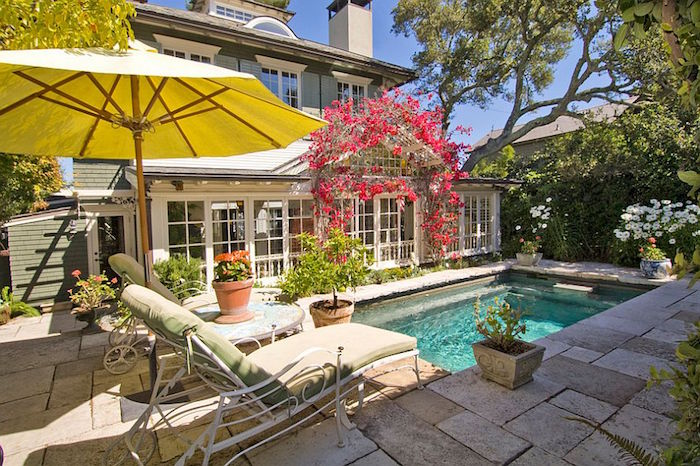 red flowers decorating the entrance of a house, small rectangular pool nearby, two sun beds, and a large yellow umbrella