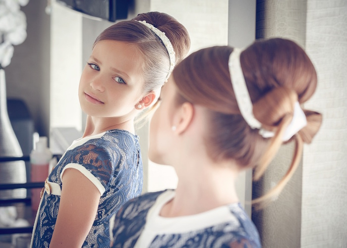 mirror reflection of a young girl, with brunette hair, tied in a bun, and a bow detail, cute girls hairstyles, navy and white lace dress, and a white hairband