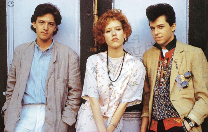red-haired actress, with short curly hair, and two young men, dressed in vintage clothes, and sporting retro hairstyles, 80s costumes men, oversized jacket and multicolored patterned shirt, lots of accessories