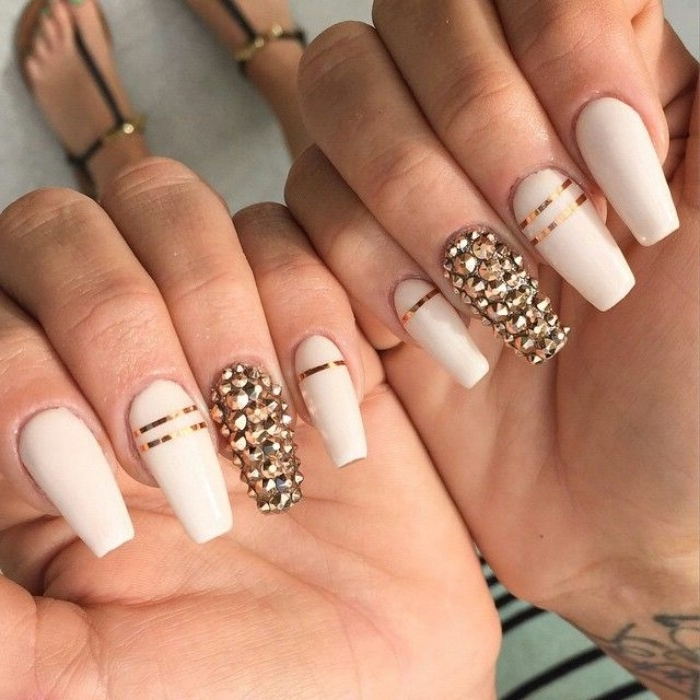 nude gel nails, with long coffin shape, in off-white, decorated with 3D, gold nail decall stickers, and metallic gold stripes