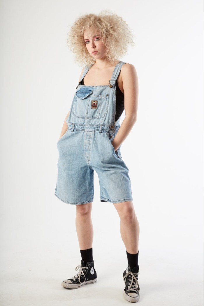 80s clothes, pale knee-length denim overalls, worn by a young woman, with voluminous blonde curly hair
