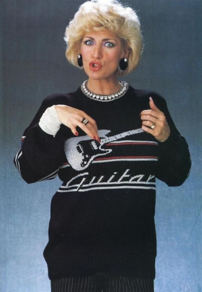 tunic sweater in black, decorated with an image of an electric guitar, and the word guitar, 80's dress up ideas, worn by a woman with short, curly blonde hair, making a funny face