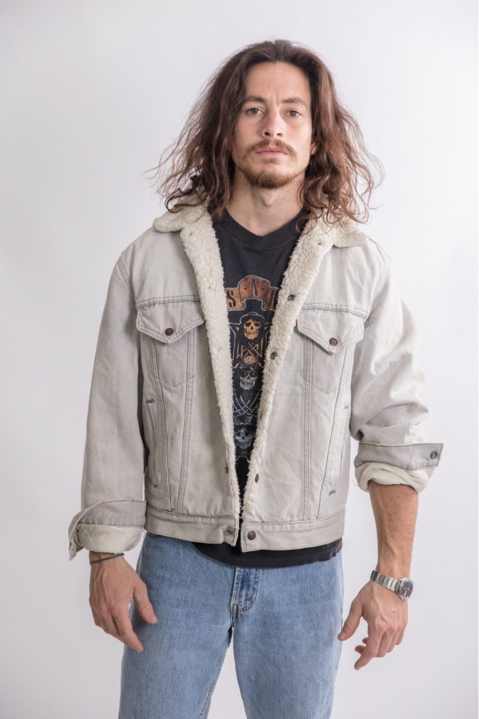 bearded man with a mustache, and shoulder length wavy hair, wearing 80s clothes, pale retro jeans, black rock band t-shirt, pale denim jacket with flannel trim