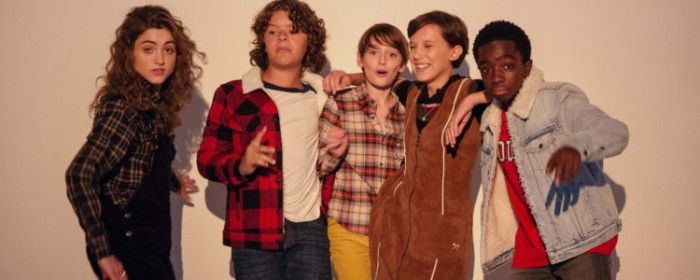 actors from the series stranger things, dressed in typical 80s outfits, plaid jackets and shirts, denim and corduroy