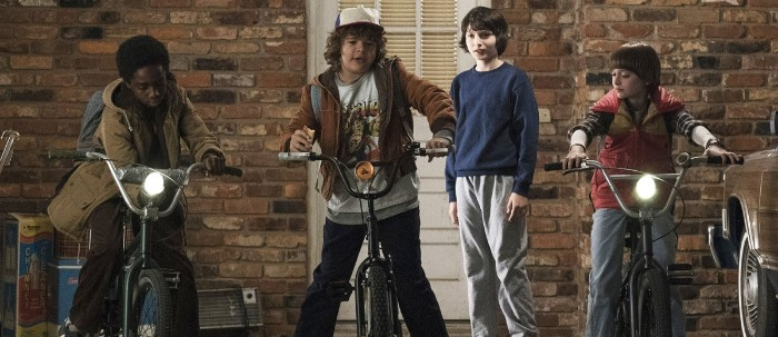 four child actors, from the television series stranger things, dressed in 80s costumes, printed t-shirts and jeans, tracksuit bottoms and corduroy jackets